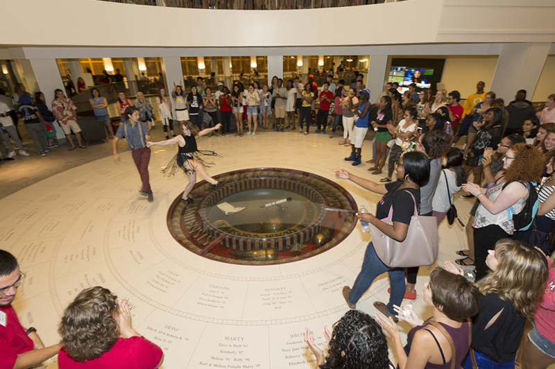 Swing dancers dance on the seal in the Armstrong Student Center while an encircling crown watches