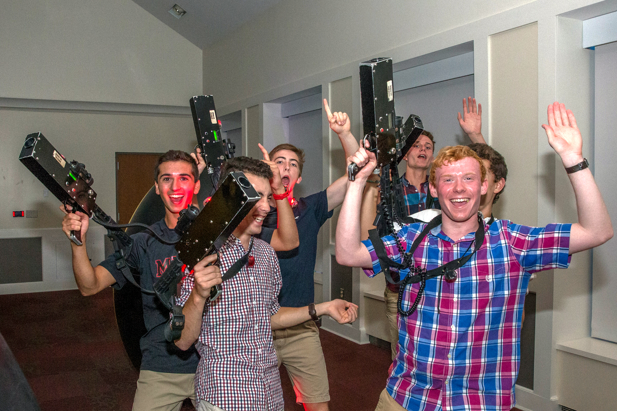 Students smile and hold laser tag gear