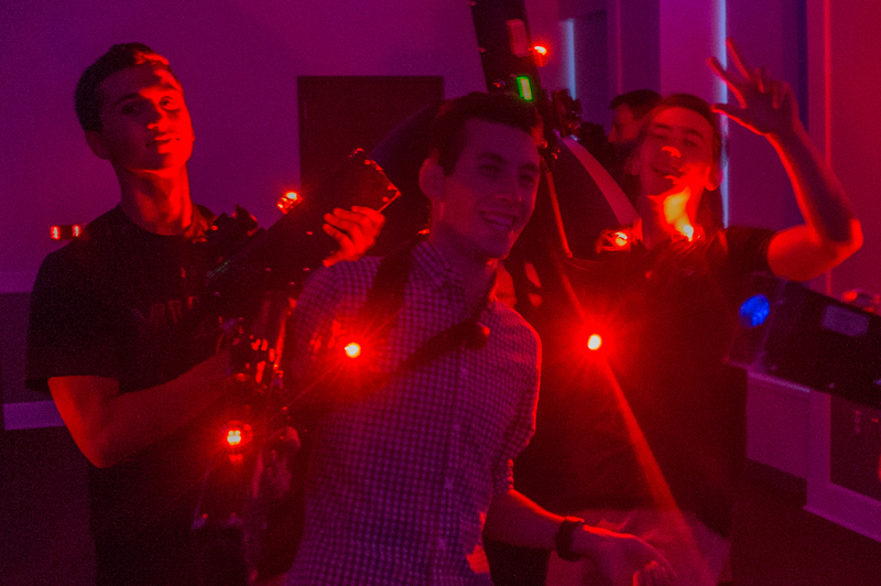 Students shoot red lasers from laser tag gear