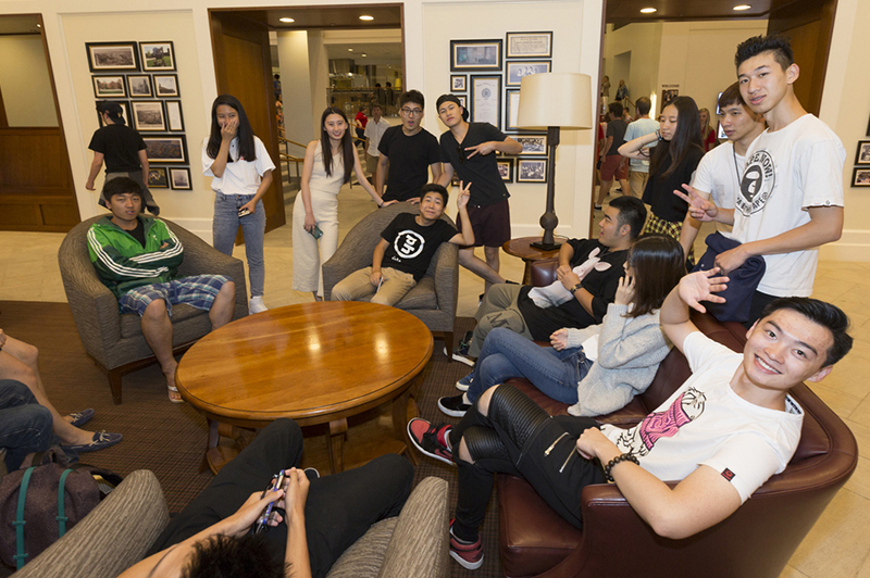 A large group of students converse on chairs and couches in Armstrong