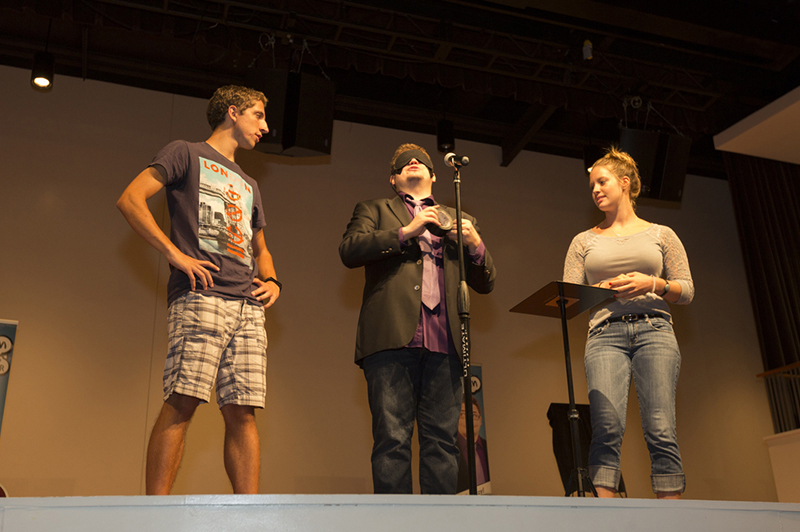 A performer and two students stand on the stage in Wilks Theater