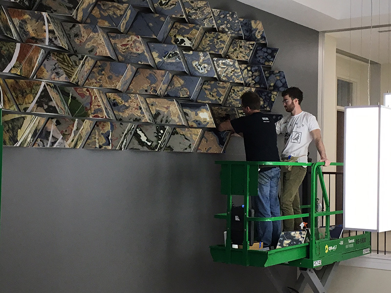 Workers install the new artwork in Shideler Hall, which was recently renovated.