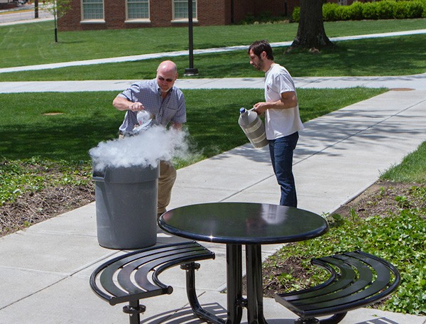 Miami faculty prep the trashcan for the volcano experiment.