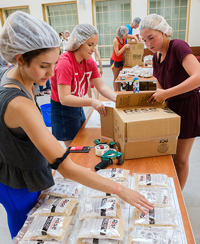 Students pack food boxes for those in need.