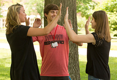 Three students particpate in a break-the-ice excercise at summer orientation.