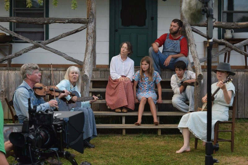 In a scene from 'The Mountain Minor' film, Warren and Judy Waldron (left) play music as Amy Cogan Clay and Jonathan Bradshaw, seated on porch, and others watch.