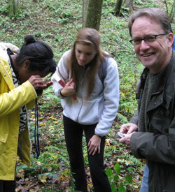 Nicholas Money and students examine botany specimens in the field