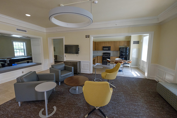 Chairs, tables and kitchen in residence hall community area