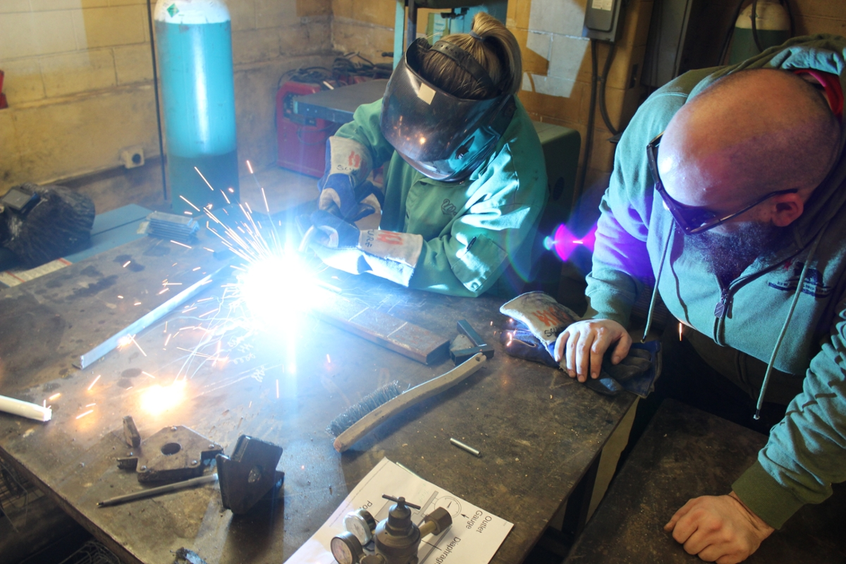 Miami advanced sculpture students welding to fabricate 'Sound of Music.'