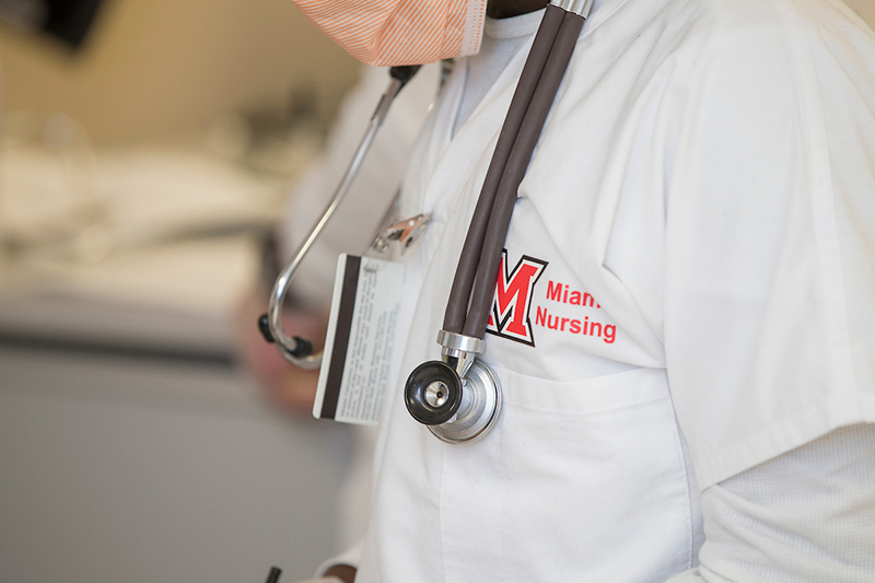 A midsection view of a Miami nursing student wearing scrubs and a stethoscope around their neck.