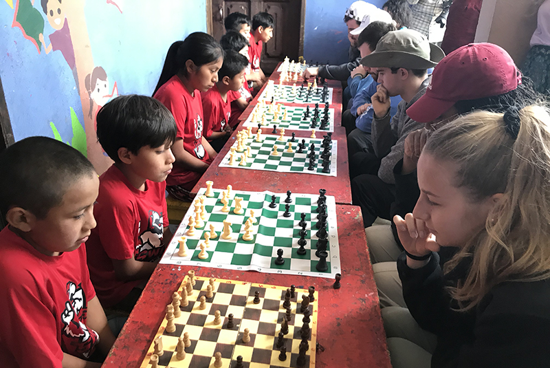 Children play chess with Miami students