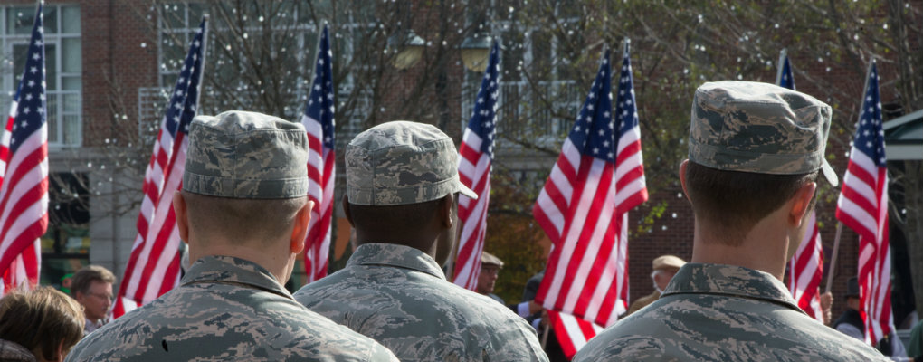 Uniformed members of the military face a bank of flags in a Veterans Day event