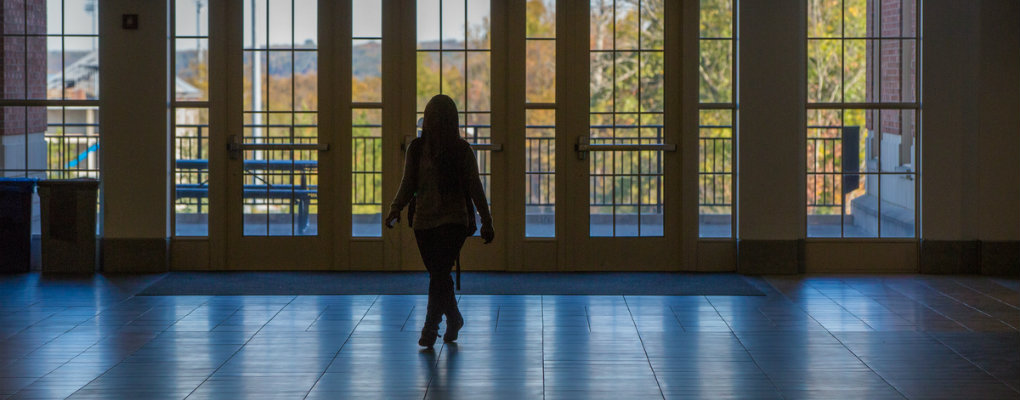 A woman is silhouetted against the door of the Armstrong Student Center