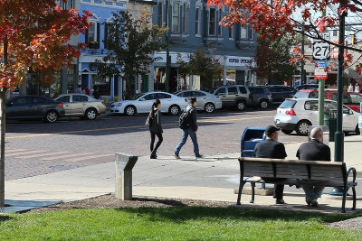 Students walking across street in Uptown Oxford. Two men sitting on a bench.