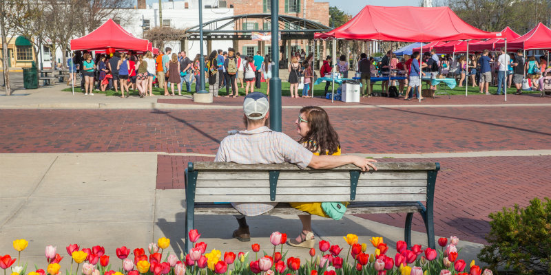 Couple view an uptown festival from park bench