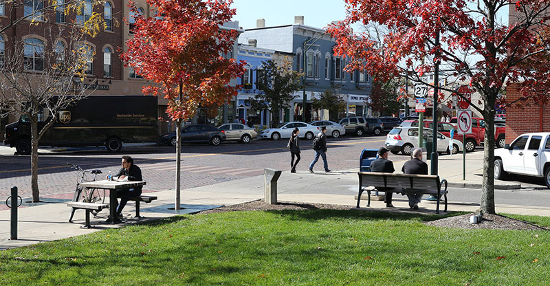 Man seated at picnic table in uptown Oxford