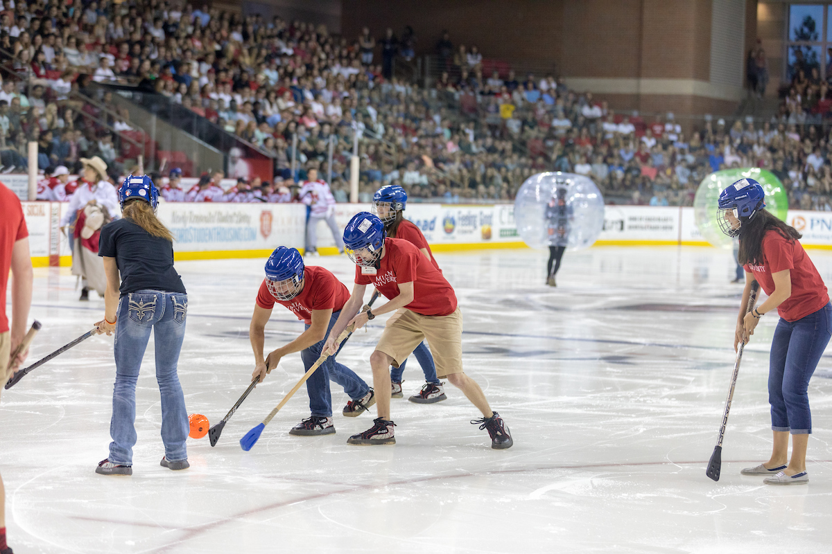 New students get their first experience playing broomball and bumperball on ice