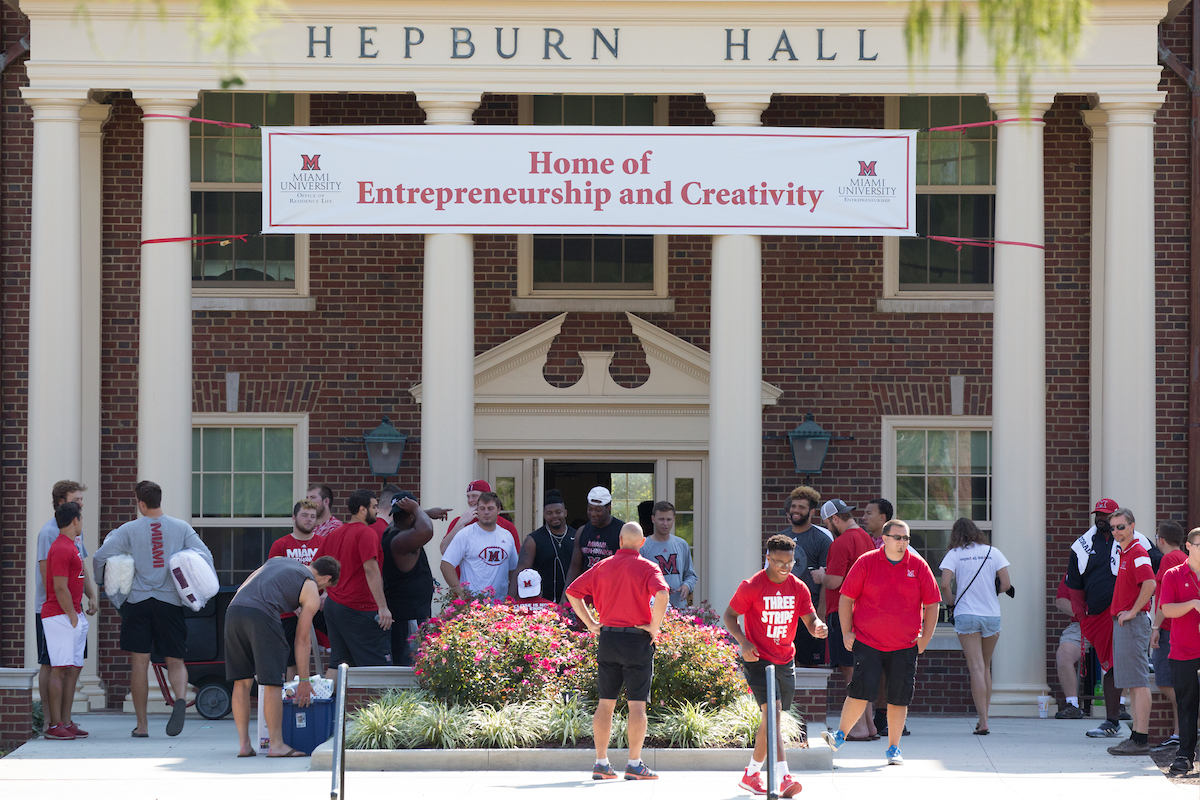 Miami student and staff volunteers gather in front of Hepburn hall ready to help new students move in.