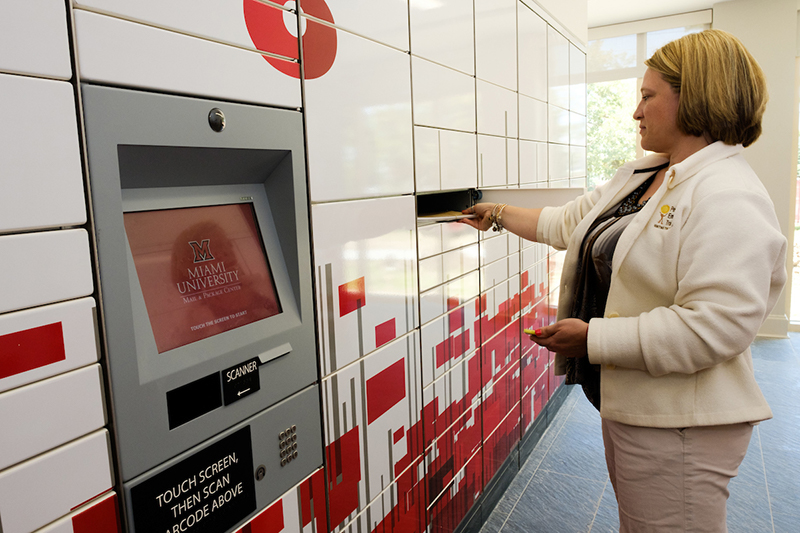 Miami staff member removes a package from one of the red and white patterned lockers in the newly renovated mail center