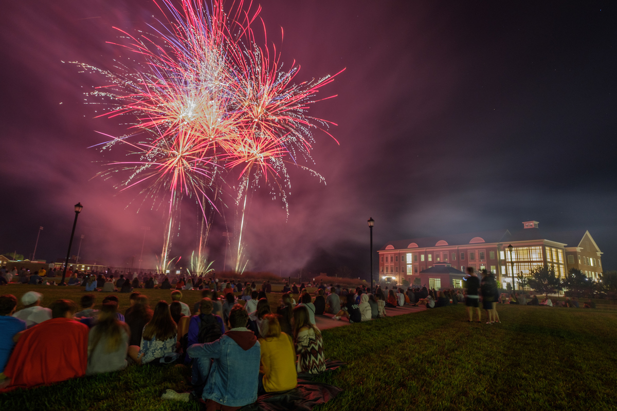Fireworks erupt over the Engineering quad as students look on