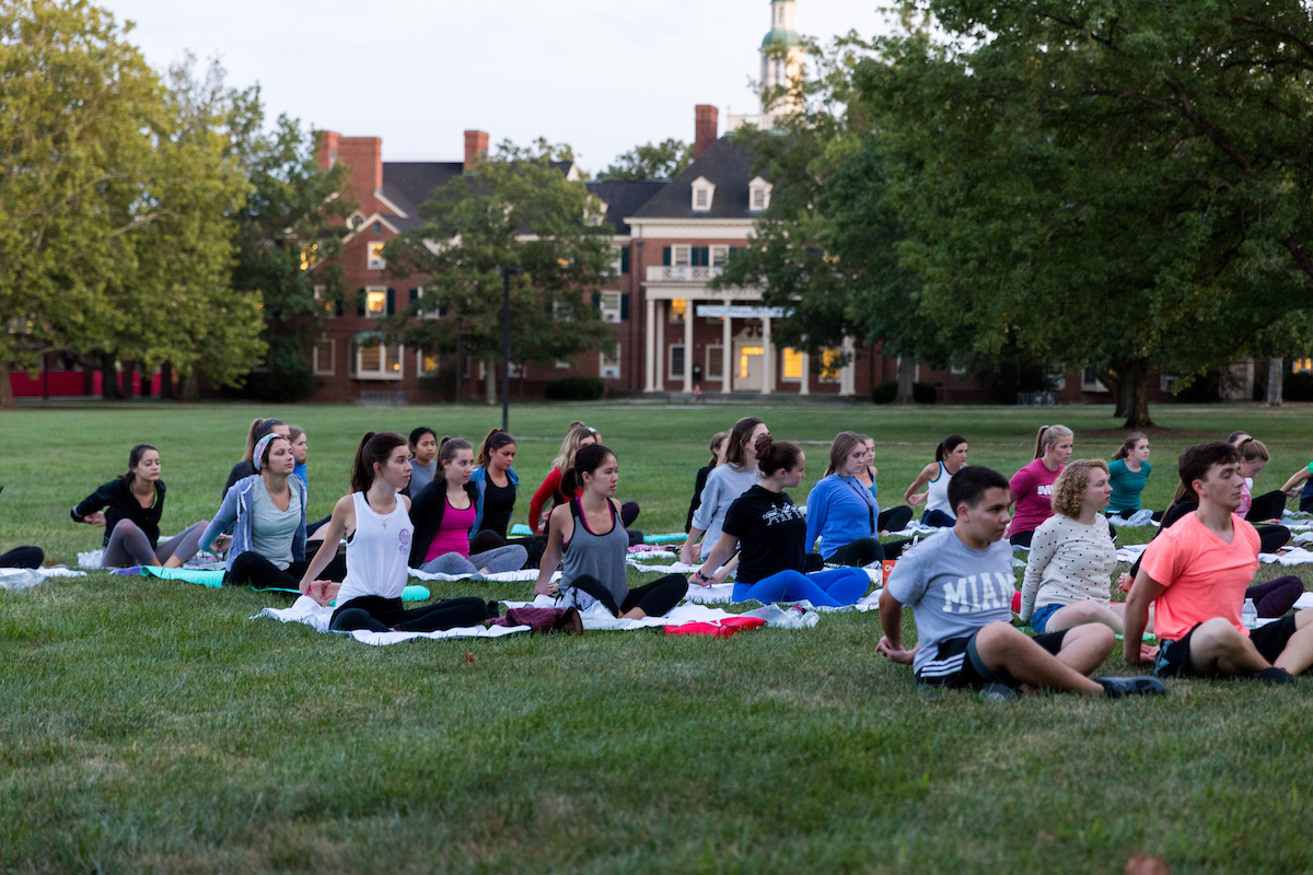 A group of students practicing yoga in the grassy quad with MacCracken Hall in the background