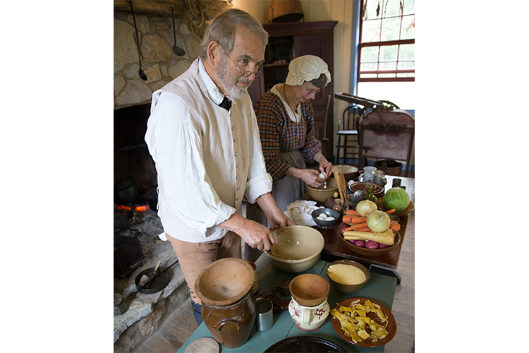 Actors portraying people from history as they prepare food for cooking in a stone fireplace