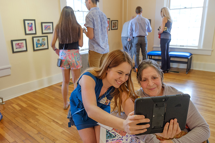 A young woman and an older woman smile as they look at a tablet computer screen together