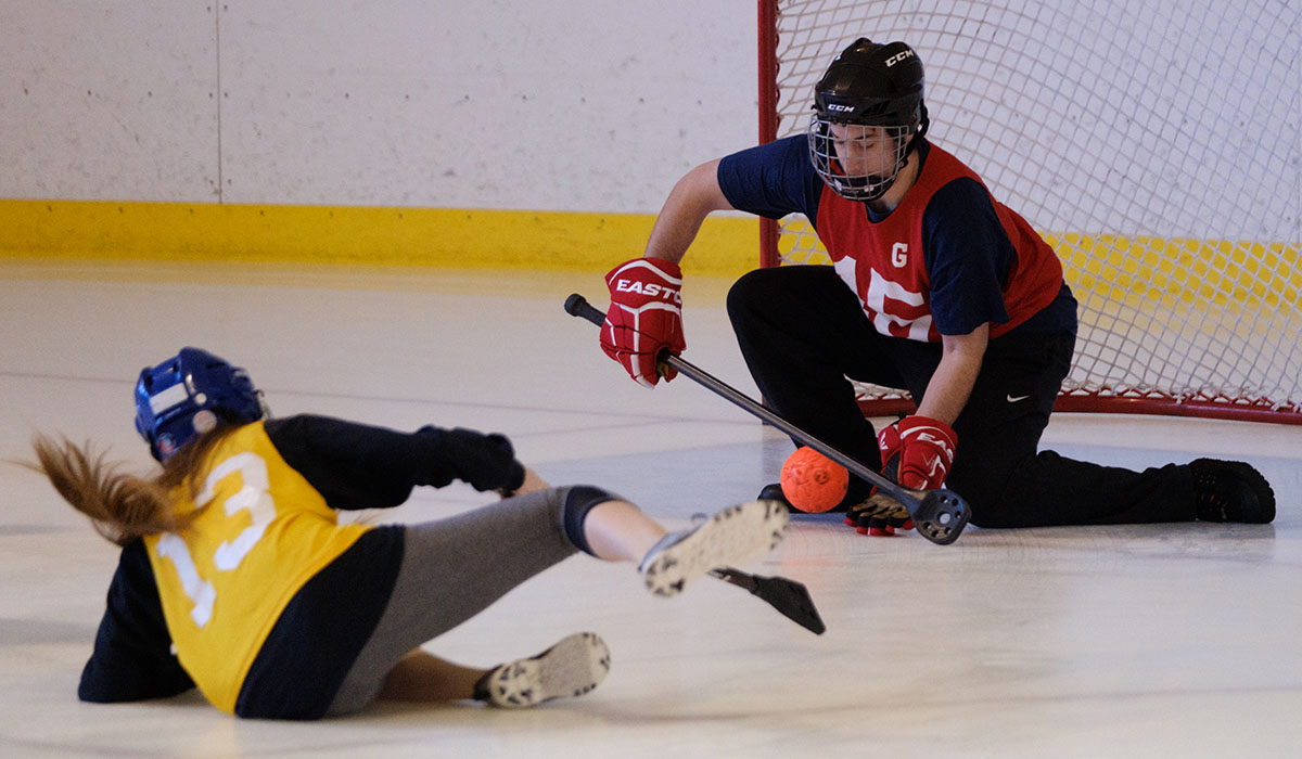 student making a shot on goal during a broomball game