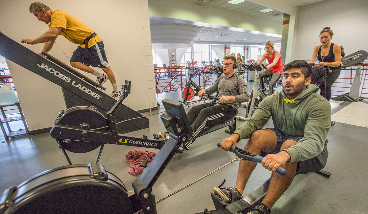 students and staff using various machines at the Rec