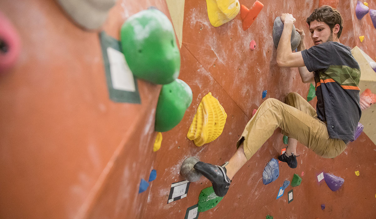 student climbing the rock wall