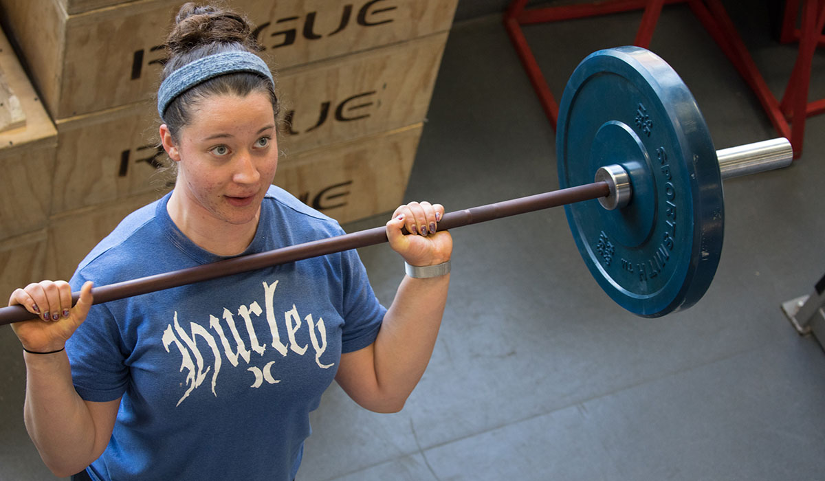female student lifting a barbell