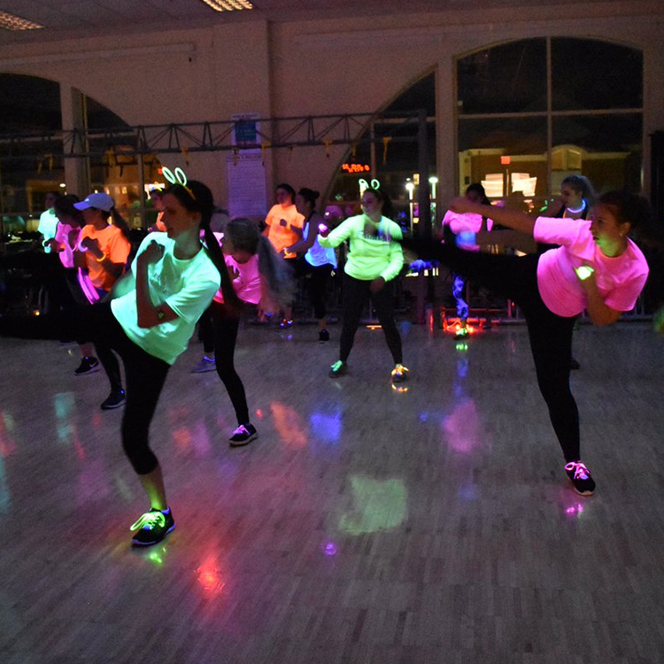 A group exercise class wearing glowing clothes and accessories exercise under a blacklight.