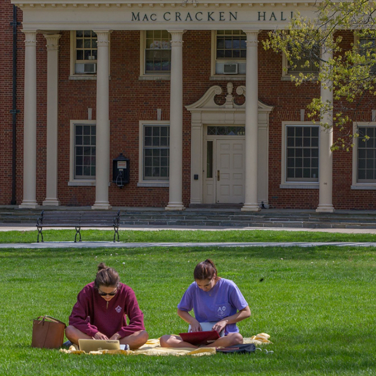 Two students studying outside of MacCracken Hall