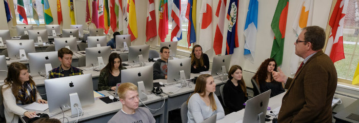 Professor speaks to his class in language lab, CAS
