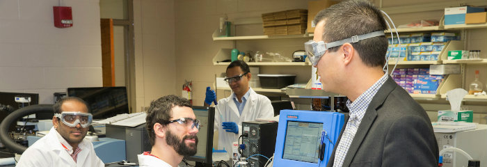 Professor Scott Hartley, wearing protective glasses, talks with students in the lab, CAS
