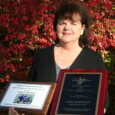 Linda Marchant holding two research awards