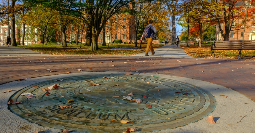 A student walks near the seal of Miami during fall