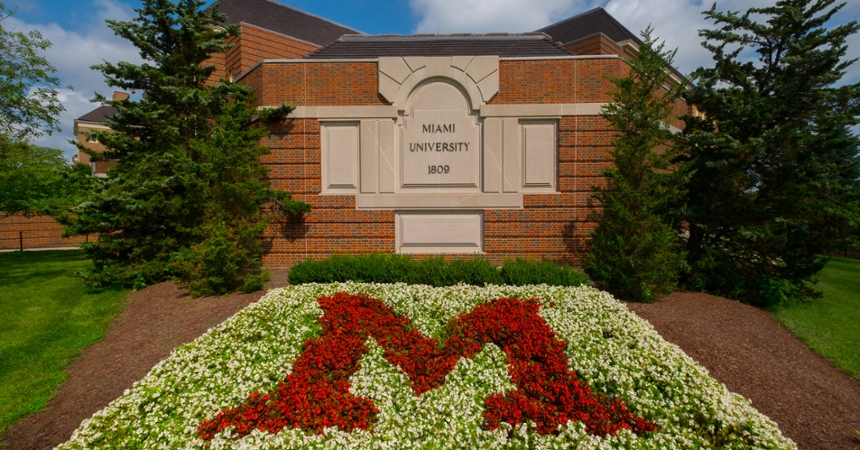A flowerbed in front of Pearson Hall forms a red