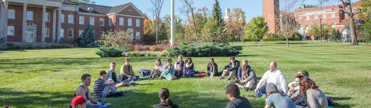 A professor and students hold class on the lawn of Roudebush Hall