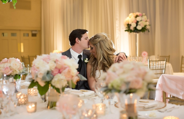 A bride and groom sitting among floral arrangements.