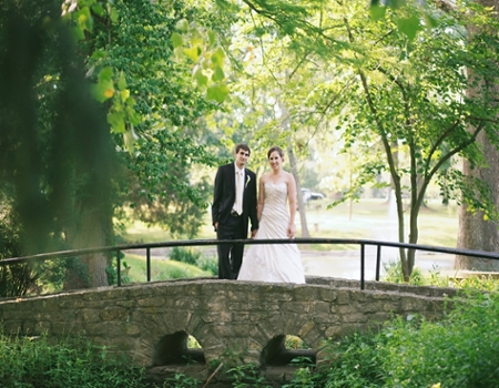 A bride and groom on the bridge near the Conrad Formal Gardens.