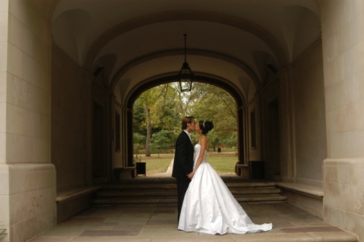 A bride and groom kiss under the Upham Arch.