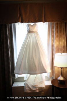 A bride's dress framed by a window and light spilling in to the room.