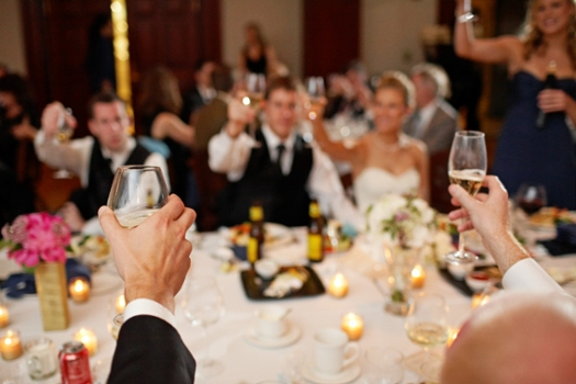 A wedding party raising their glasses for a toast.