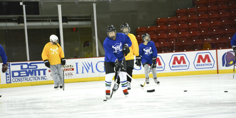 Blue and yellow hockey teams playing