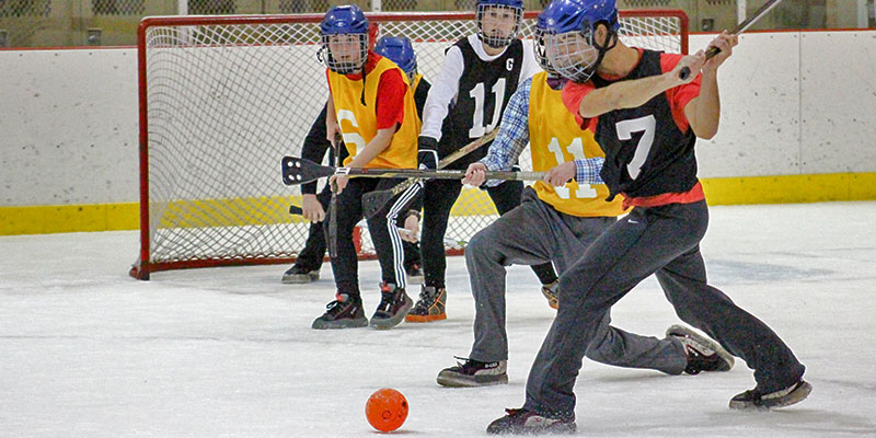 Student shooting a goal in broomball