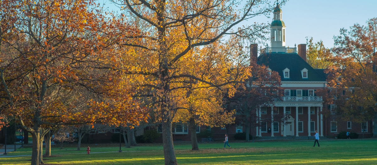 Wide shot of MacCraken Hall in the fall with students walking in past.