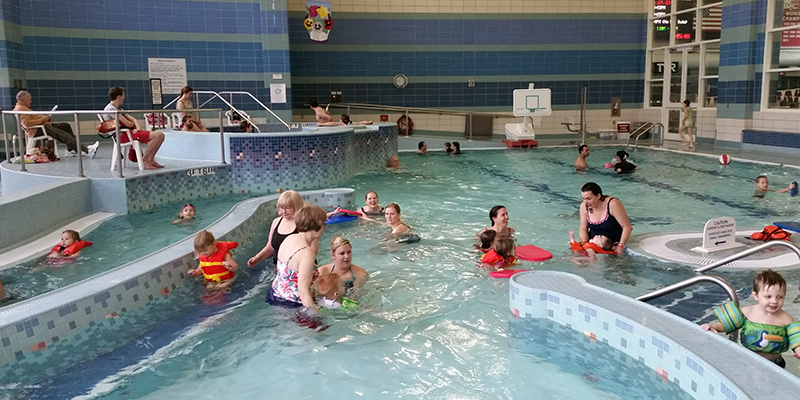 Families swimming in leisure pool during Family Fun Day.