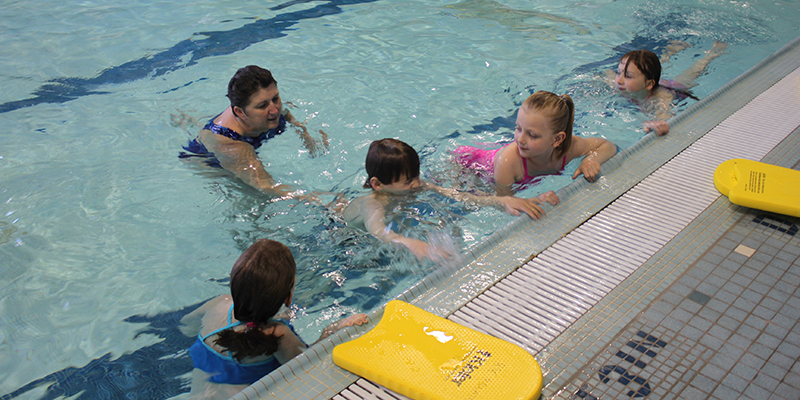 Swimming instructor teaches group of children in Miami