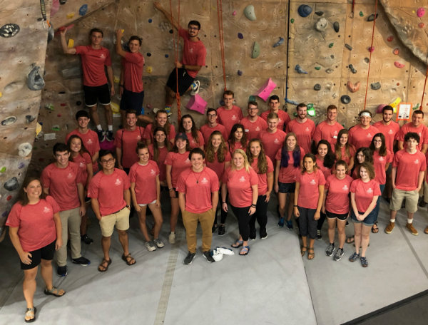 group of people standing in front of climbing wall